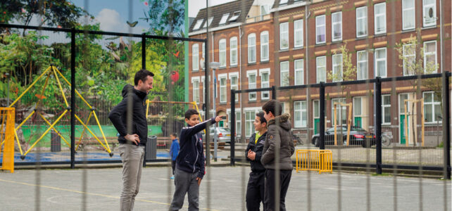Father and kids playing in a school playground in BoTu, Rotterdam.