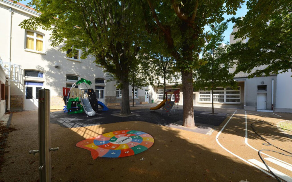 Example of a resilient schoolyard in Paris that is open to the community, offers greenspace, and has solar panels on the roof, while it protects against heat waves,  and capture and drain off floodwater via permeable ground.