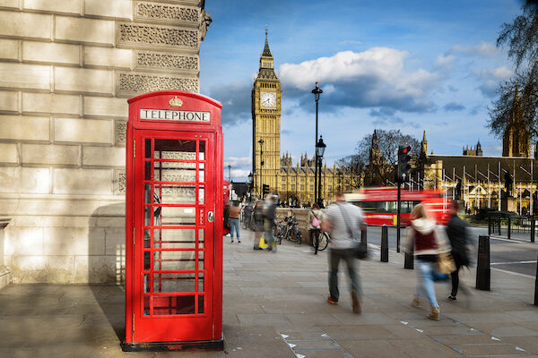 Red phone box with Big Ben, with people waling on the streets of London.