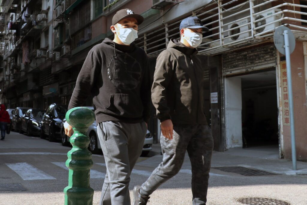 Two young men walk down a city  street wearing disposable covid face masks.