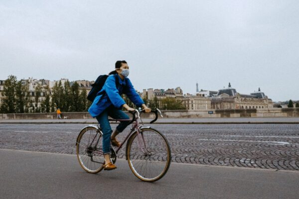 Man wearing denim riding a bike on an empty paris street, with a covid mask
