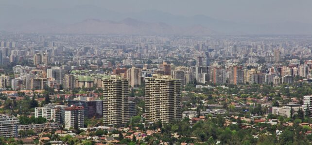 Skyline of Santiago, Chile on a sunny day. behind the buildings, haze or smog somewhat obscures rolling hills.