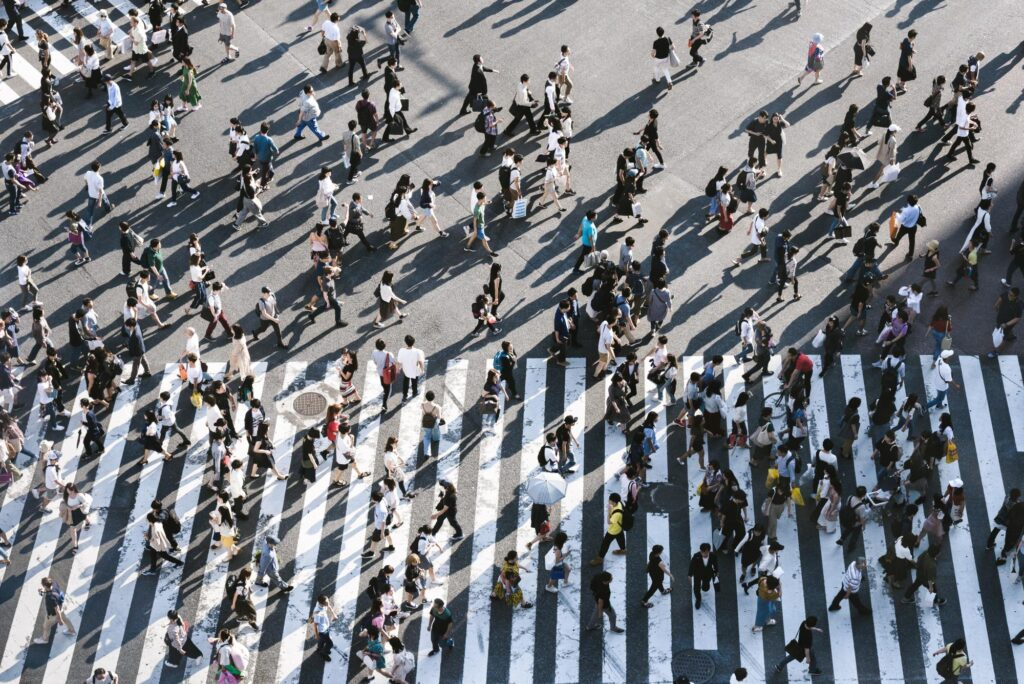 View from above showing hundreds of people walking across a large crosswalk in a city on a sunny afternoon.