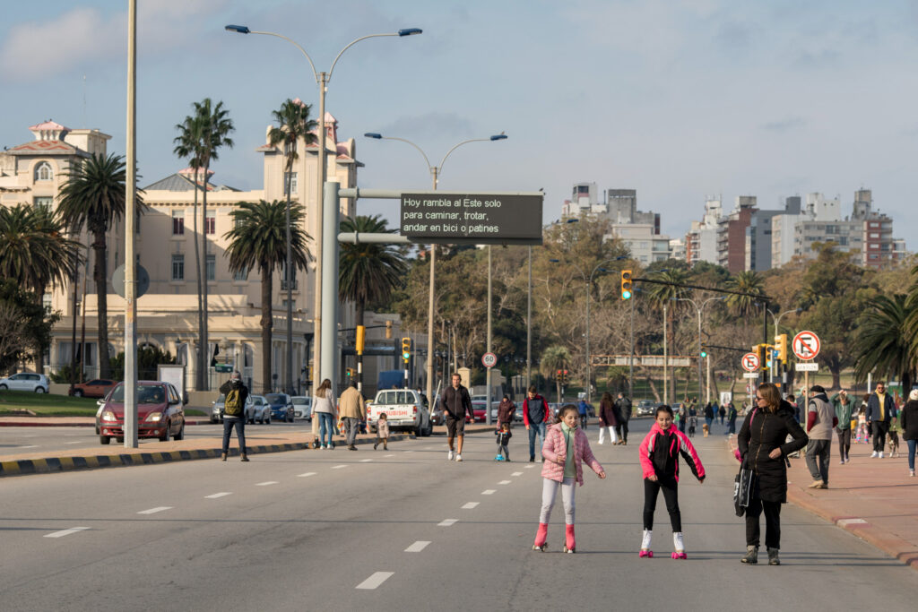 People enjoy a relaxing walk, or ride scooters or roller skates, on a Montevideo street that has been closed to cars for the day.