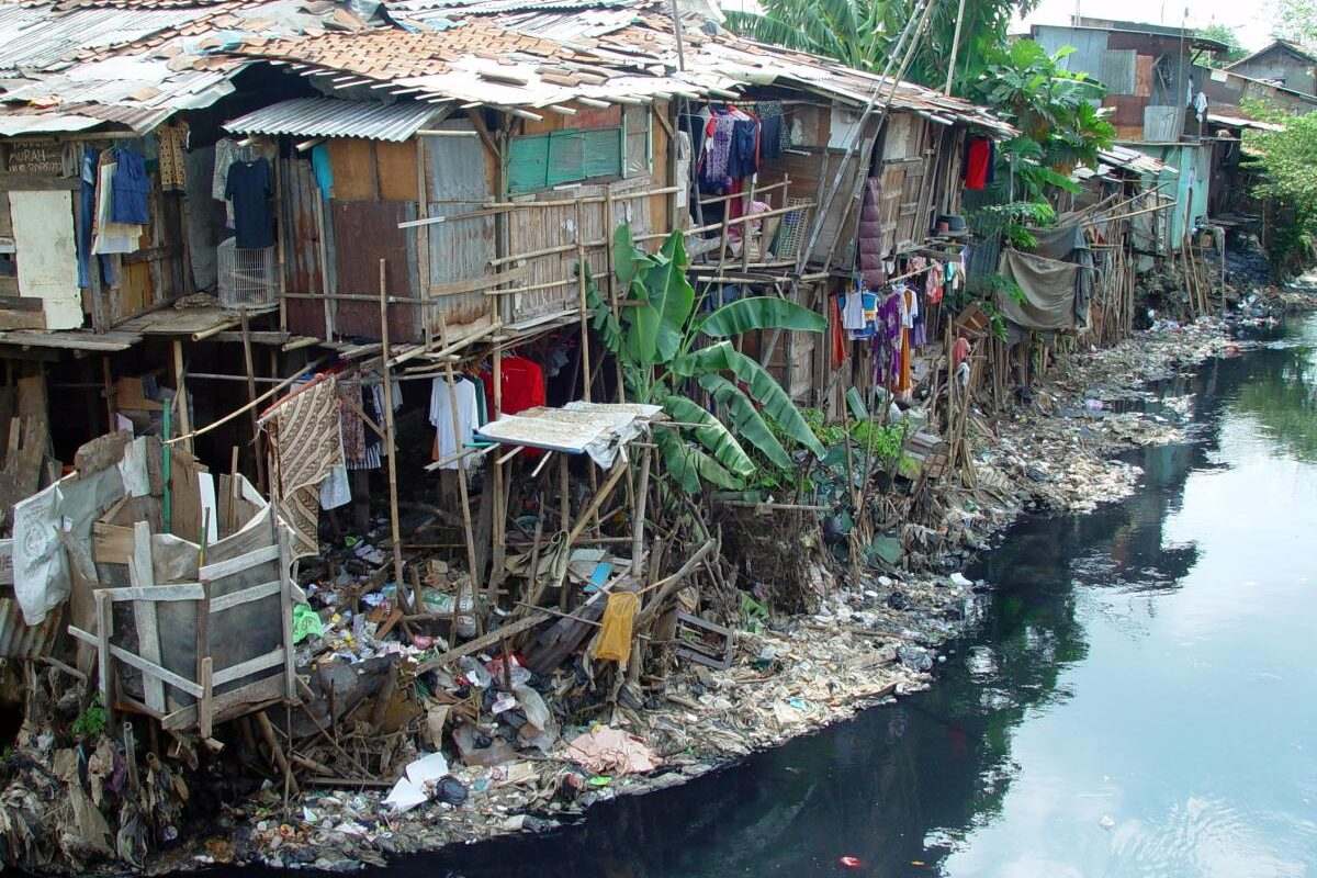 wooden slums in Jakarta stand along the side of a river polluted with trash.