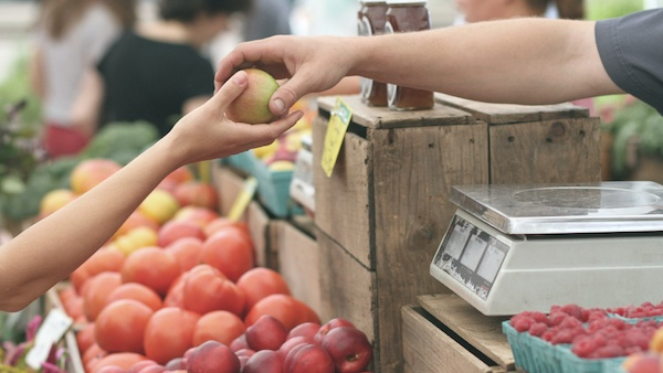 Hands of two people delivering and receiving an apple in a food market.