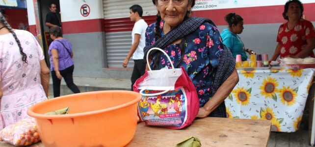 Old woman in Oaxaca, Mexico buying groceries on the street with diverse people walking around.