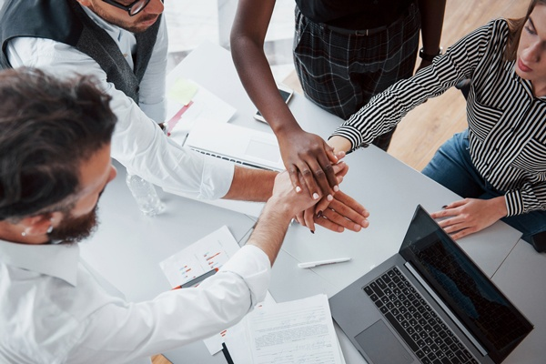 Young business people discussing joining their hands as a team during meeting in an office.