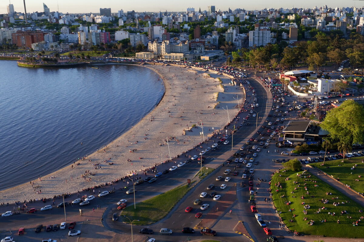 A wide shot from above Montevideo shows buildings along the skyline among trees, a beach next to a bay on the left populated with people enjoying sunset, a park full of picnicers on the right, and busy streets full of cards between the beach and the park.