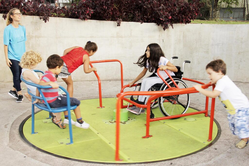 Several children play on, push, and ride a handicap-accessible merry-go-round set in a clean, cement playground