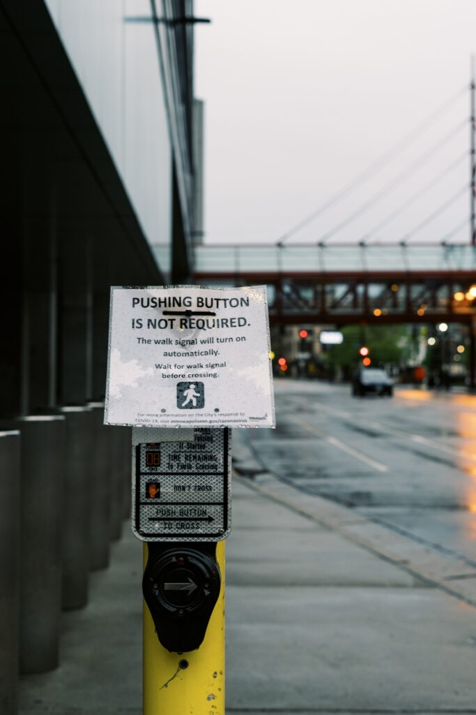 "Minneapolis, MN, USA - a printed sign taped over a crosswalk button reads ""PUSHING BUTTON IS NOT REQUIRED."" Photo by Weston MacKinnon on Unsplash."