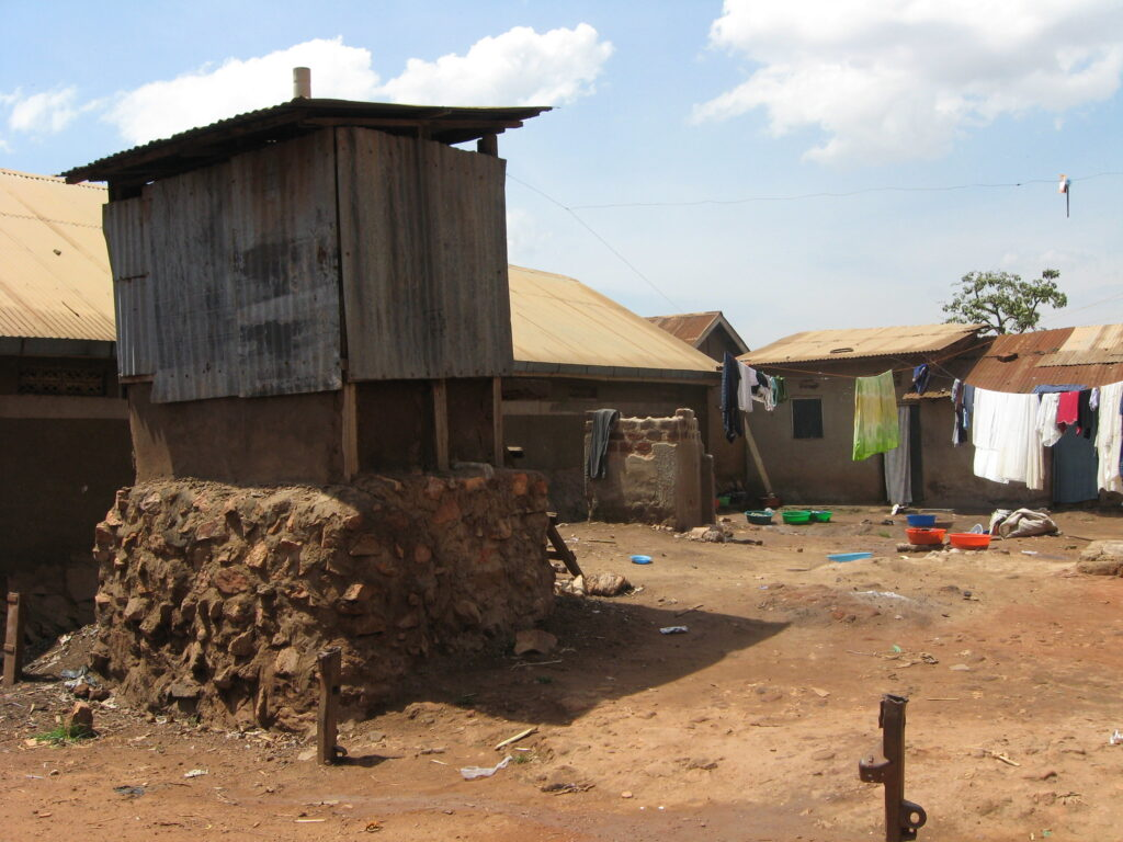 A corrugated tin shack serves as a latrine in Kampala, sitting on an earthen foundation, in a dirt square of a semi-rural slum.