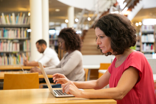 Serious focused middle-aged woman working on research in a public library. Adult students sitting at desks and using laptops.