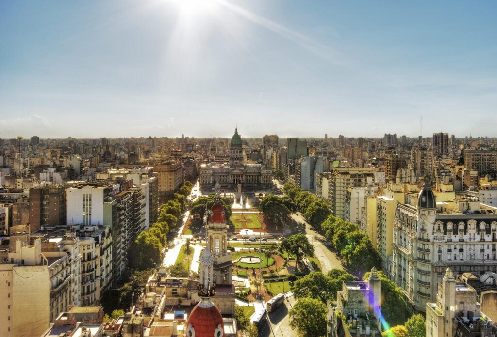 A bright sun shines down on the Palacio del Congreso, in Buenos Aires, Argentina, full of modern and traditional buildings, greenery, and people.