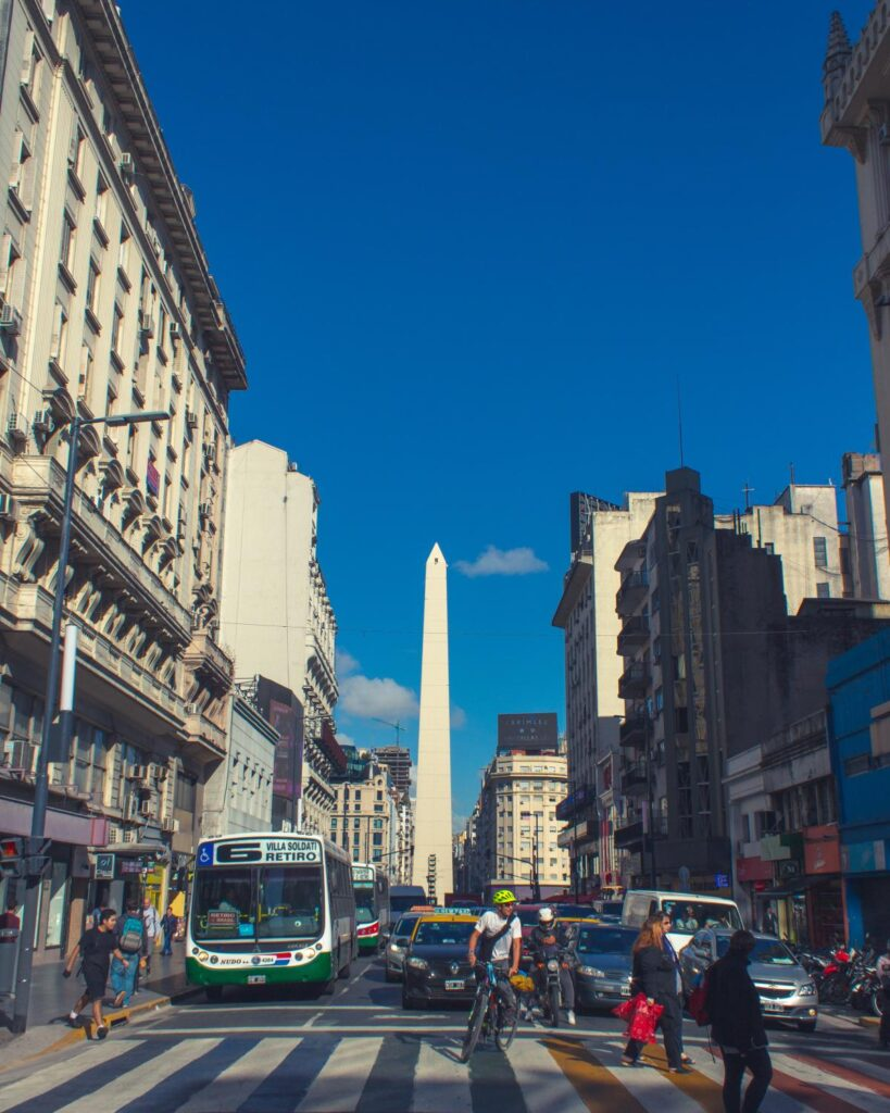Street level view of the obelisk monument in Buenos Aires, Argentina. People on bikes, pedestrians, and busses and cars fill the street in the foreground, with tall buildings lining both sides of the street and the obelisk against a bright blue sky in the background.
