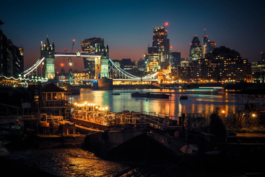 Tower Bridge of London lit up at night, against a dusky skyline with boats on the river in the foreground.