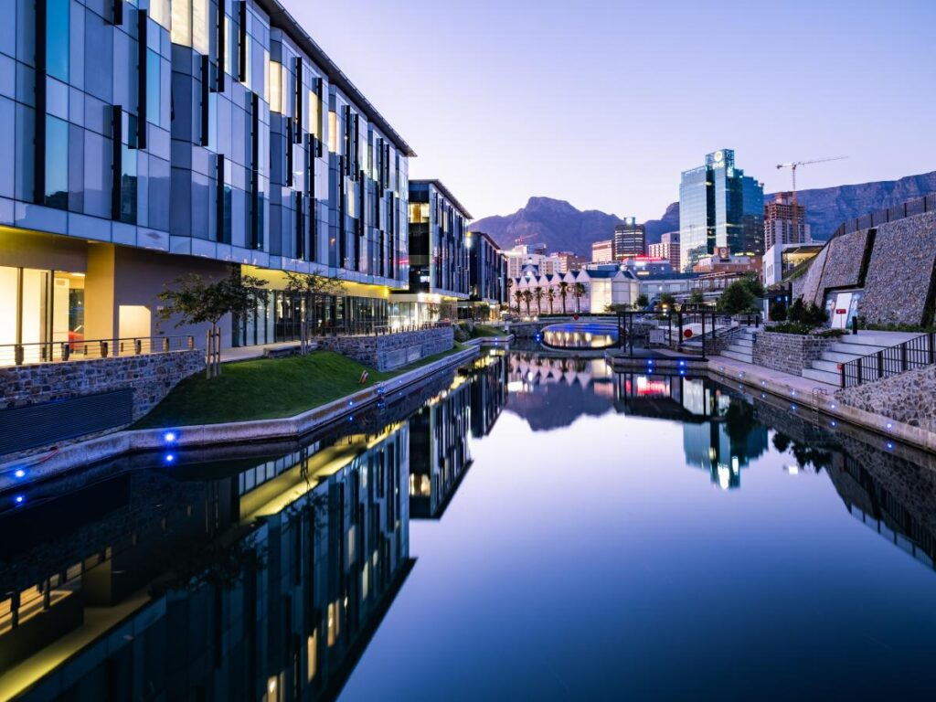 An urban canal shows sunset at dusk, in a modern city of glass and steel, with beautiful mountains in the background.